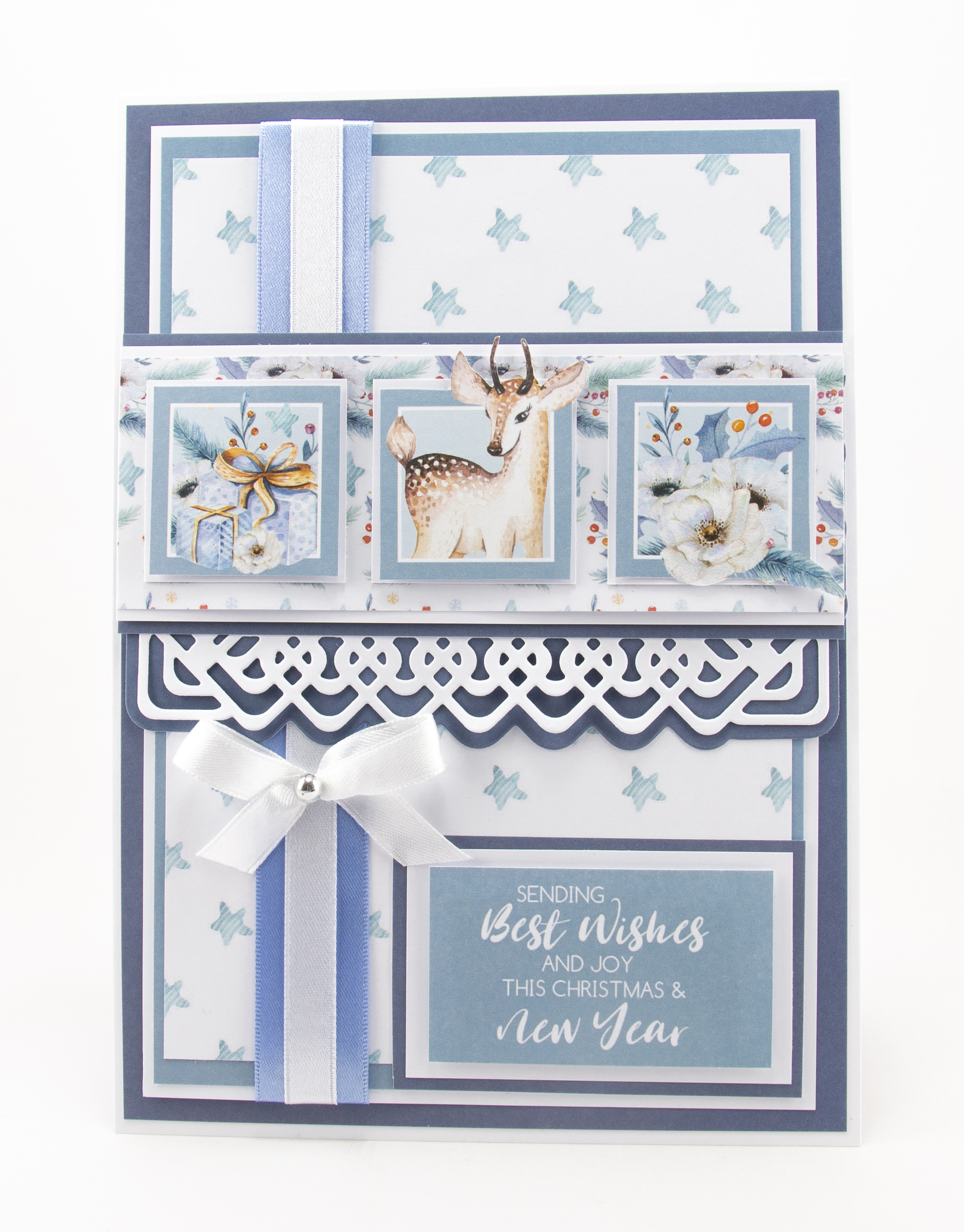 A Christmas card with a star backing paper, a deer image, presents and Christmas Roses